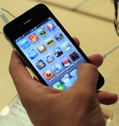 A customer looks at an iPhone 4 at the Apple Store 5th Avenue in New York, in this June 24, 2010 file photo. Apple Inc came clean on July 2, 2010 about an embarrassing software glitch that overstates network signal strength in its hot-selling iPhone, as complaints mounted about the phone's wraparound antenna. Apple admitted its signal strength miscalculation dates back to its original 2007 iPhone. It promised to fix the glitch in a few weeks, but did not directly address concerns that its antenna design causes reception problems for iPhone 4, its newest phone.  REUTERS/Eric Thayer/Files (UNITED STATES - Tags: BUSINESS SCI TECH)